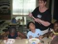 Barb Ziegler helping Freedom School scholars paint their butterflies